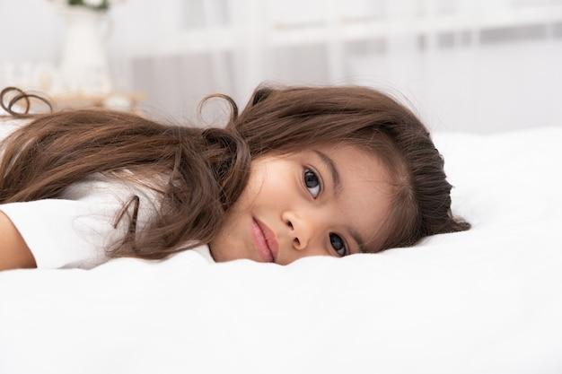 Portrait of little brunette girl lying on bed at home.