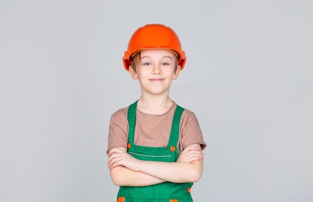 안전모에 세로 작은 작성기. 어린이 건물 헬멧, 안전모. 헬멧에 작은 작성기. 일꾼 빌더로 분장한 아이. 헬멧을 쓰고 어린 소년입니다.