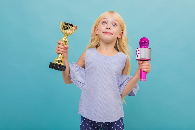 Portrait of little caucasian girl in blue t-shirt with long blonde hair holds a gold cup and microphone isolated on blue