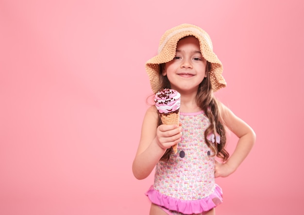 Portrait of a little cheerful girl in a summer hat with ice cream in her hands, on a colored pink background, summer concept