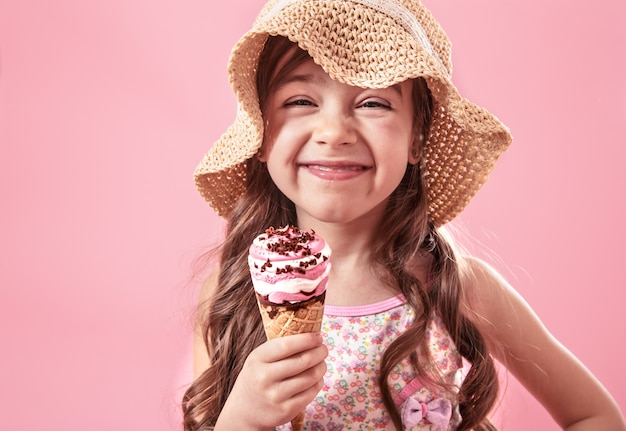 Portrait of a little cheerful girl with ice cream on a colored wall