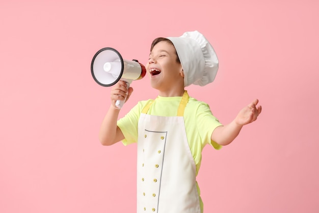 Portrait of little chef with megaphone on color