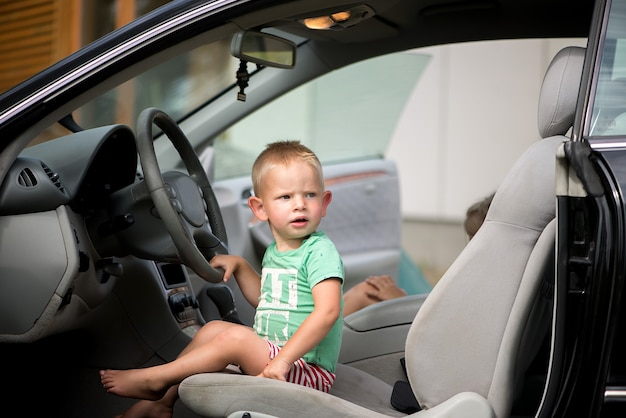 A portrait of a little child boy sitting at the wheel of a car