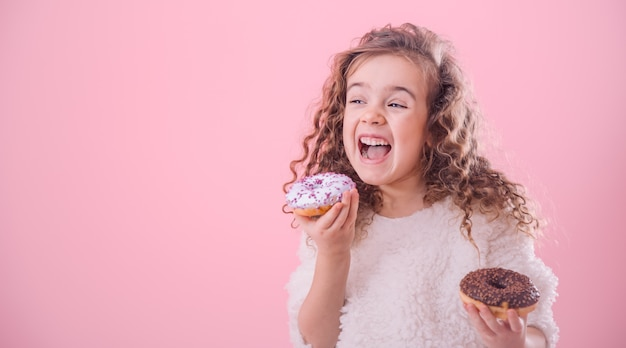 Portrait of a little curly girl eating donuts