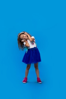 Portrait of little curly girl in white shirt playing with big wireless headphones, listening to music, singing song and dancing with closed eyes on blue