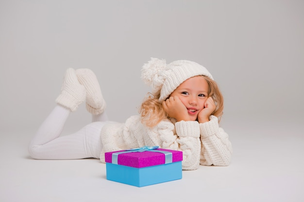 Portrait of a little curly-haired girl in a knitted white winter hat