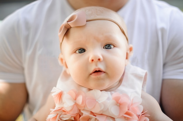 Portrait of little cute baby girl in father hands