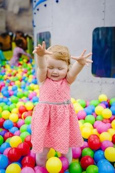Портрет маленькой милой девочки принцессы младенческой 1-2 года стоя и играть с воздушными шарами, красочными шарами на детской площадке, ямой для мячей, сухим бассейном для вечеринки по случаю дня рождения. концепция празднования первого года.