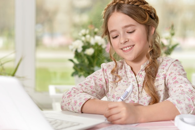 Portrait of a little cute blonde girl using computer