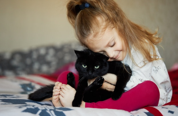 Portrait of a little cute child girl who hugs a black cat with tenderness and love and smiles with happiness