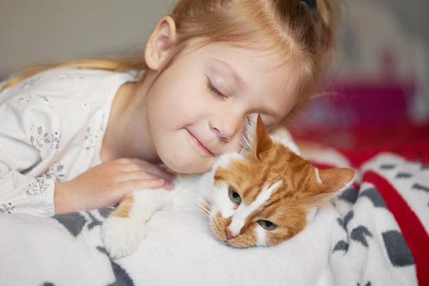 Portrait of a little cute child girl who hugs a redhead cat with tenderness and love and smiles with happiness