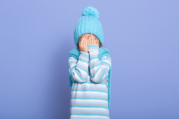 Portrait of little cute girl covering her eyes with hands,