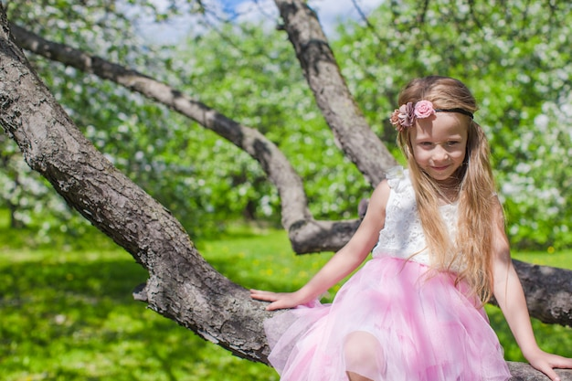 Portrait of little cute girl sitting on blossoming apple tree