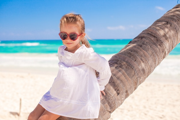 Portrait of little cute girl sitting on palm tree at the perfect caribbean beach