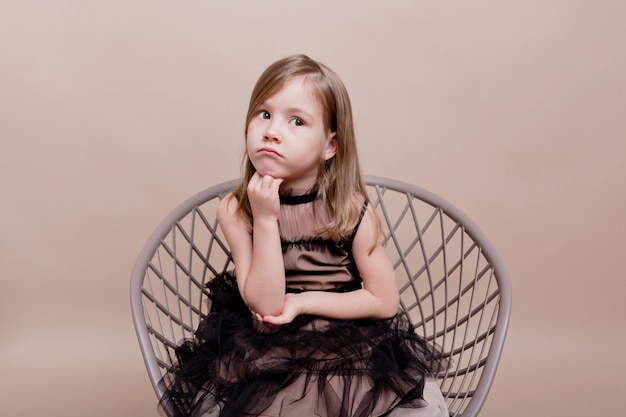 Portrait of little cute girl wears black dress sitting in chair with a pensive face and posing on isolated wall, real serious motions of pretty charming girl