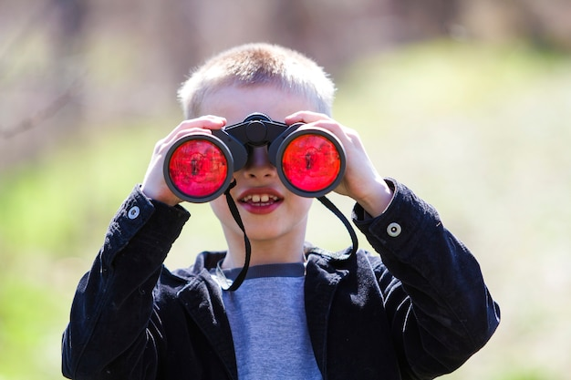 Portrait of little cute handsome cute blond boy watching intently something through binoculars in distance on blurred .