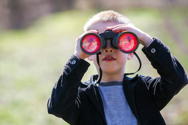 Portrait of little cute handsome cute blond boy watching intently something through binoculars in distance