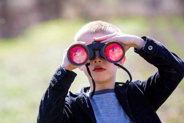 Portrait of little cute handsome cute blond boy watching intently something through binoculars