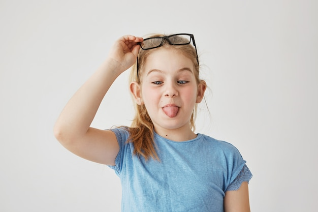 Portrait little cute miss with blue eyes and light hair in blue t-shirt funny posing with mow eyes, showing tongue and raising glasses. copy space.