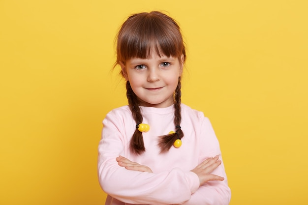 Portrait of little dark haired girl with folded hands posing over yellow