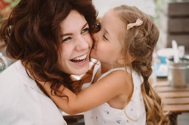 Portrait of little daughter kissing her beautiful happy mother outdoors