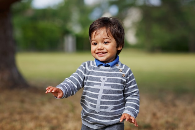 Portrait of a little eastern handsome baby boy playing outdoor in the park
