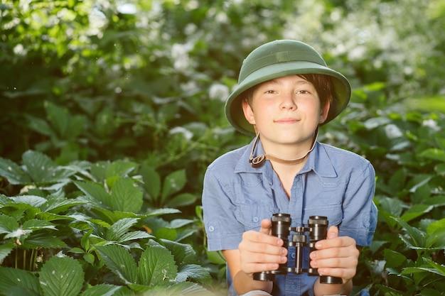 Portrait of little explorer with binoculars in forest