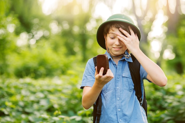 Portrait of little explorer with map and compass in forest
