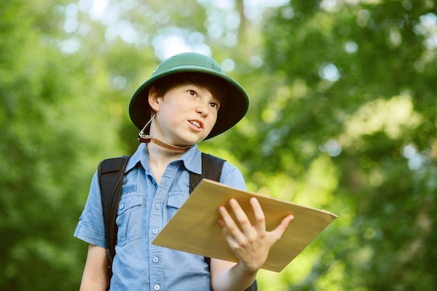 Portrait of little explorer with map in forest
