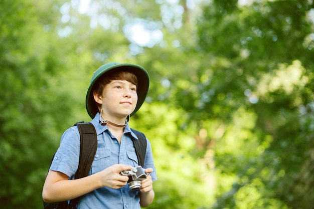 Portrait of little explorer with photo camera in forest
