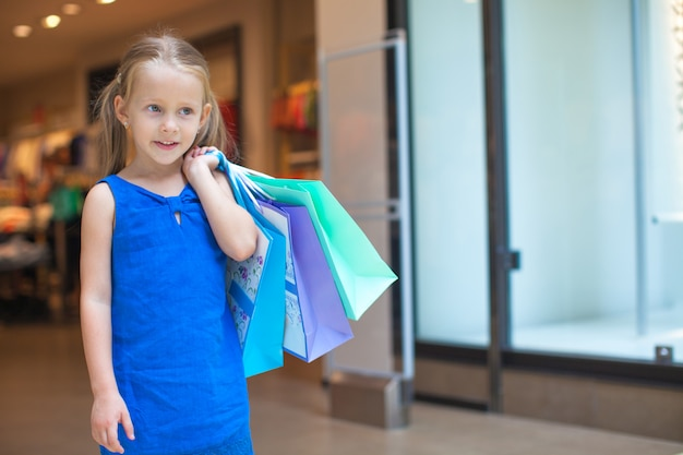 Portrait of little fashion girl holding shopping bags at the mall
