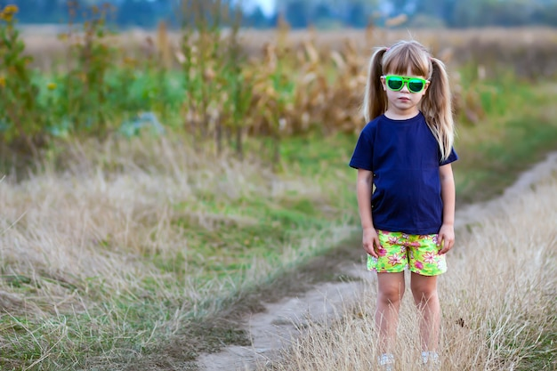Portrait of little fashionable girl in green sunglasses outdoors