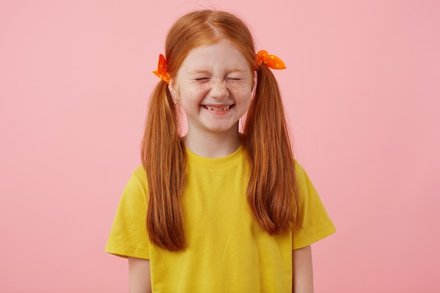 Portrait of little freckles red-haired girl with two tails, smiles with closed eyes, wears in yellow t-shirt, stands over pink background.