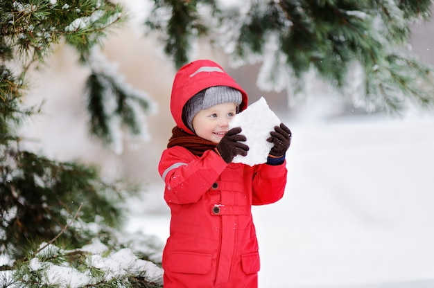 Portrait of little funny boy in red winter clothes having fun with piece of ice.