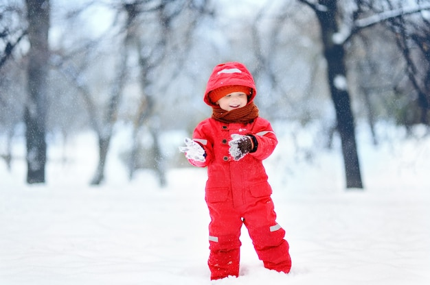 Portrait of little funny boy in red winter clothes having fun with snow during snowfall.