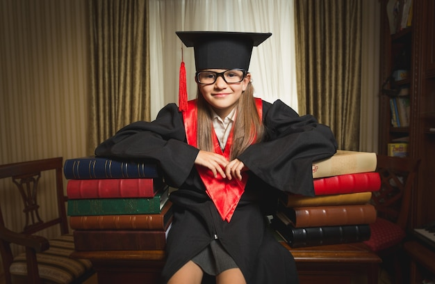 Portrait of little genius girl in graduation clothes leaning on books at library