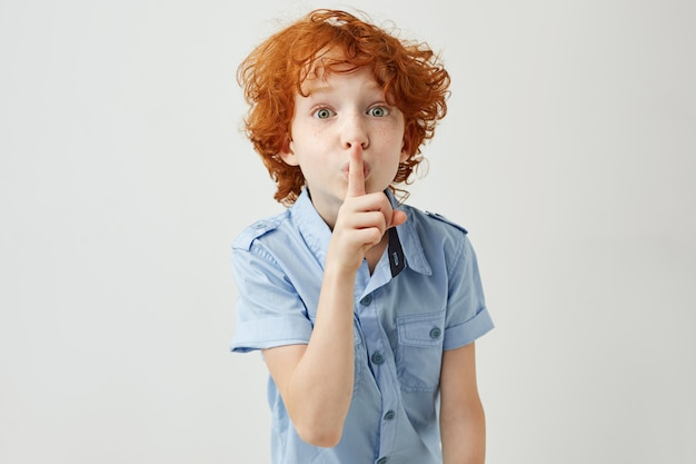Portrait of little ginger boy with curly hair and freckles holding finger near lips