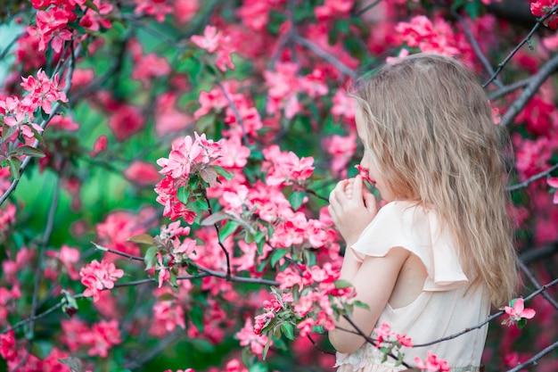 Portrait of little girl in beautiful blooming apple garden outdoors