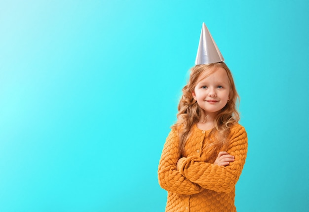 Portrait of a little girl in a birthday hat.