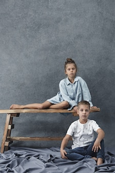 A portrait of little girl and a boy on the gray wall