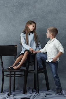Un ritratto di bambina e un ragazzo sul muro grigio