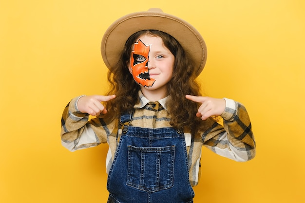 Portrait little girl child with halloween makeup mask looking confident with smile on face, pointing oneself with fingers proud and happy, posing isolated over yellow color background wall in studio