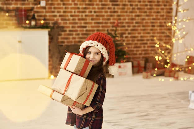 A portrait of a little girl in a christmas decorated house in a christmas hat
