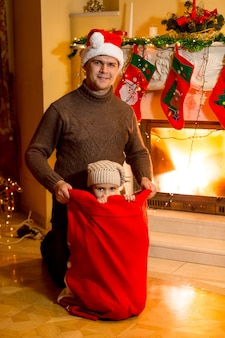 Portrait of little girl climbed in santa red bag, man holding bag