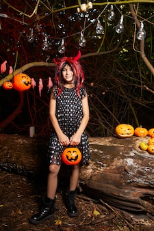 Portrait of little girl in devil costume  while standing at halloween party in the dark