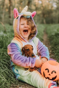 Portrait of little girl and a dog in halloween costumes with a pumpkin basket for sweets outdoors