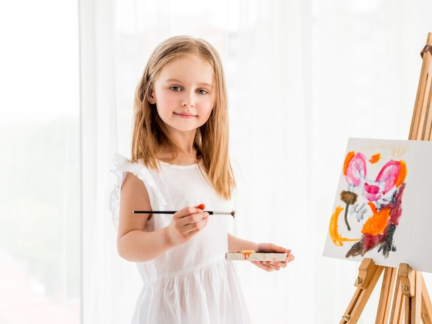 Portrait of a little girl drawing a picture on easel