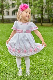 Portrait of a little girl in a dress with a bow on her head dancing on a background of green grass