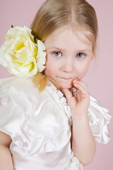 Portrait of a little girl in a dress with flower