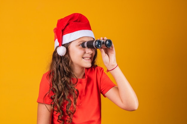 Portrait of a little girl dressed in christmas outfit looking through a binoculars.
